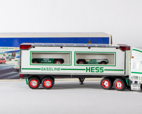 Hess truck carrying two small racecars in front of original packaging.