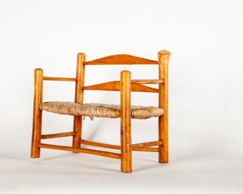 Wooden dollhouse bench. Medium tone wood and woven seat.