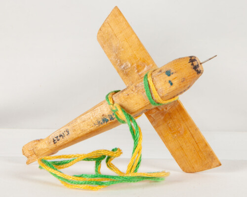 Underside of toy plane. Yellow and green twine attaches the wings to the plane.