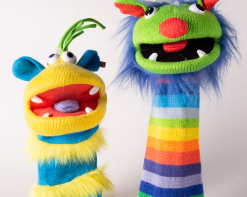 Two colorful and fuzzy monster hand puppets.