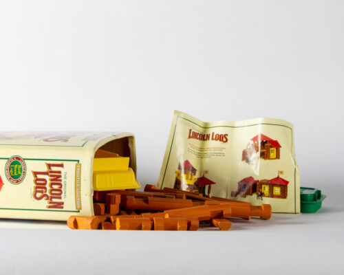 Wooden Lincoln Logs spilling out of their container.