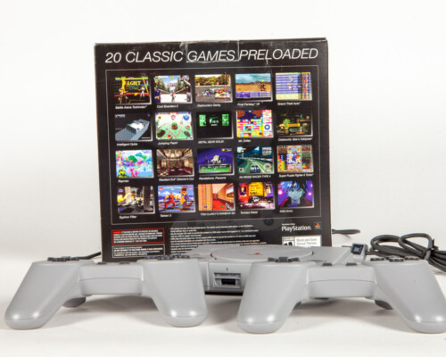 Playstation classic console with two controllers and reverse of packaging.