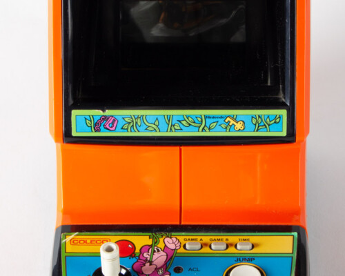 Front of Donkey Kong Jr. home console. Orange and black shell with white buttons.