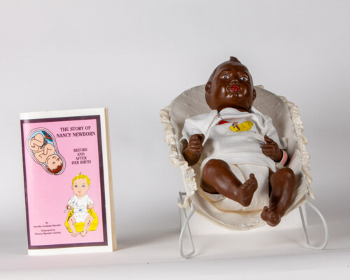 African American Nancy Newborn doll with baby seat and book.
