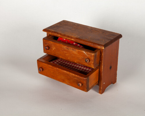 Dollhouse dresser. Darker wood with red patterned fabric peaking from drawers.