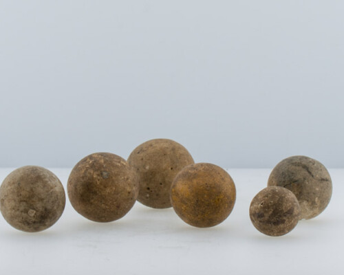 Several brown ceramic marbles of multiple sizes.