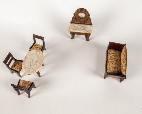 Collection of dollhouse furniture. Desk with mirror, dining table, and lounge chair.