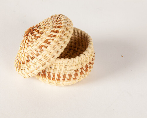Close up of small woven sweetgrass basket with matching lid.
