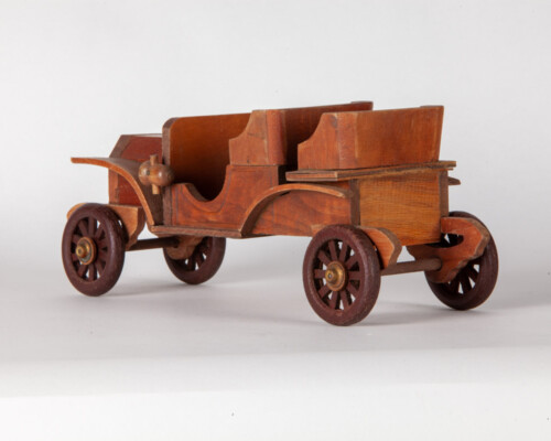Rear of wooden depiction of an early car. Several shades of wood.