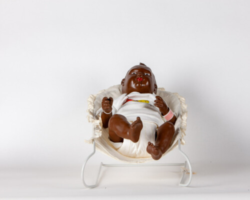 African American Nancy Newborn doll with baby seat.
