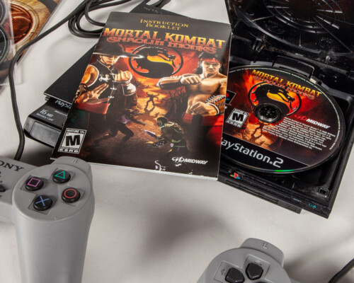 """Playstation 2 with two controllers and a copy of """"Mortal Kombat"""" in the disk tray."""
