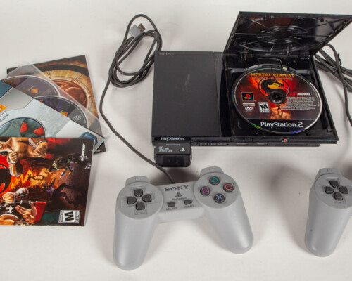 """PlayStation 2 with two controllers and """"Mortal Kombat"""" in the disk tray and other games."""