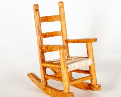 Dollhouse rocking chair. Medium tone wood and woven seat.