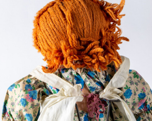 Rear view of Raggedy Anne doll with short hair and blue and tan floral dress.