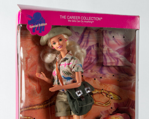 Close up of paleontologist Barbie in dinosaur print shirt with canvas bag.