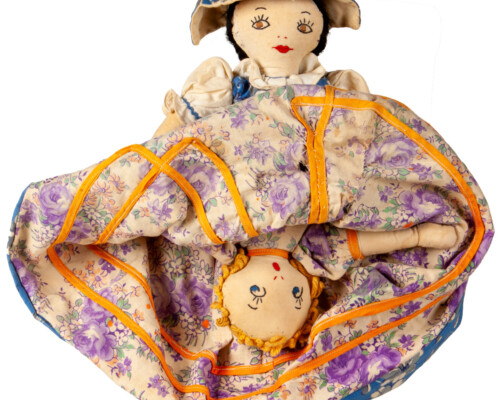 Reversible doll with both faces showing, pink and purple floral dress pattern.