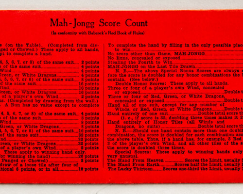 Rear side of yellow and red Mah-jongg score counter describing the scoring of the game.