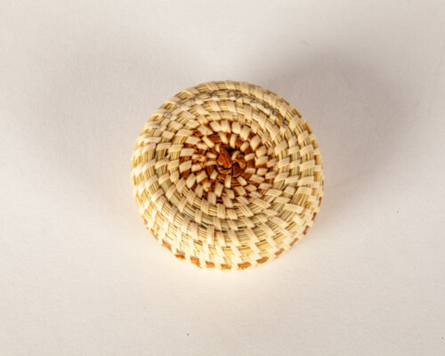 Close up of small woven sweetgrass basket.