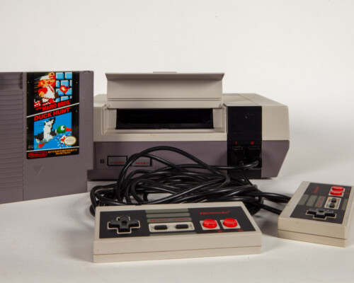 Nintendo Entertainment System with two controllers and a cartridge next to the console.