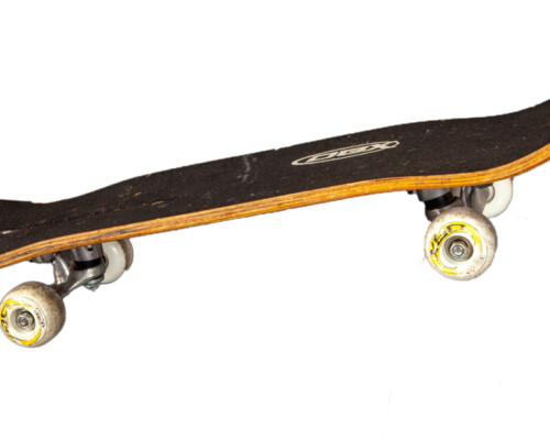 Side of DBX skateboard, shows wear on the trucks and wheels.