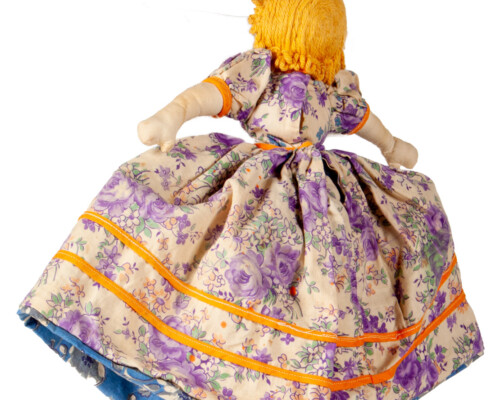 Reverse of blonde side of reversible doll. Pink, purple, and yellow floral pattern.