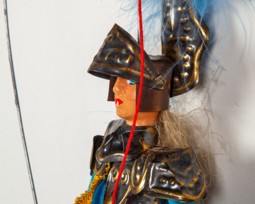 Marionette puppet depicting a knight in grey, gold, and blue clothes. Blue feathered helmet.