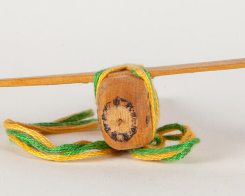 Front of Handmade toy plane. Carved image of an engine face and yellow and green twine sits below.