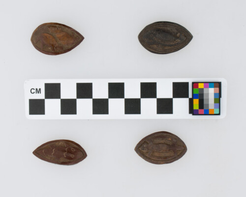 Four game tokens with animal motifs carved, arranged around a scale.