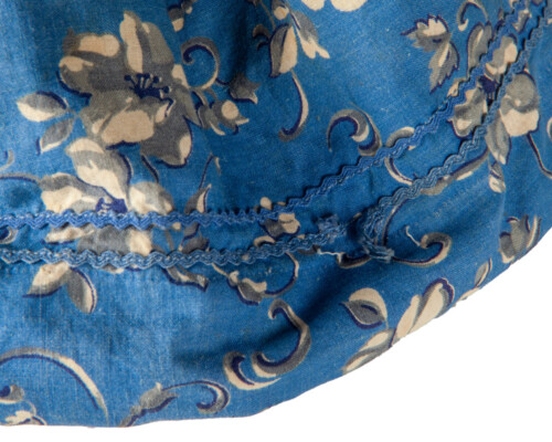 Close up of stitching on blue and pink patterned doll dress.