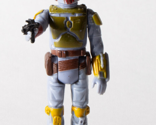 Front view of Boba-Fett action figure. Left arm raised and pointing a blaster.