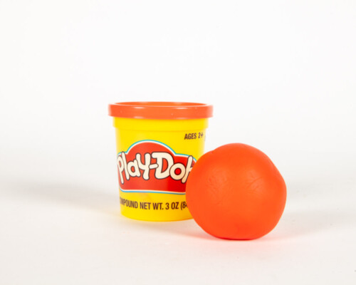 Orange Play-Doh ball next to yellow and red cylindrical container.