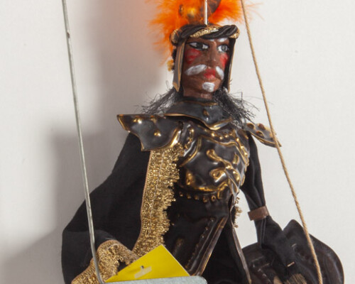 Marionette puppet of a man with a mustache wearing gold and black clothes with orange feathered hat.