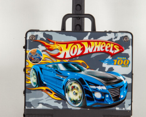 Hotwheels car container. Black box with rolling handle. Front has decal with car.
