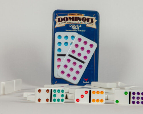 Metal box set of Dominoes. Dominoes scattered and three show their faces.