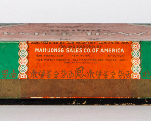 Side label of antique Mah-Jongg game box. Chinese dragon and text motifs.