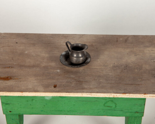 Close up of dollhouse water jug and basin on wooden dollhouse table.