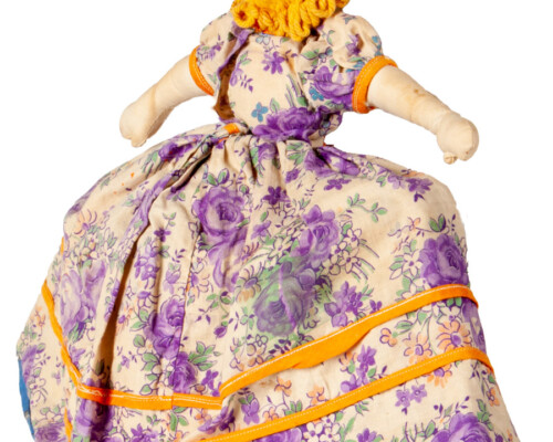 Rear side of blonde doll with blue and tan floral dress.