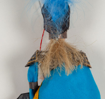 Reverse of marionette puppet depicting a knight in grey, gold, and blue clothes. Blue feathered helmet.