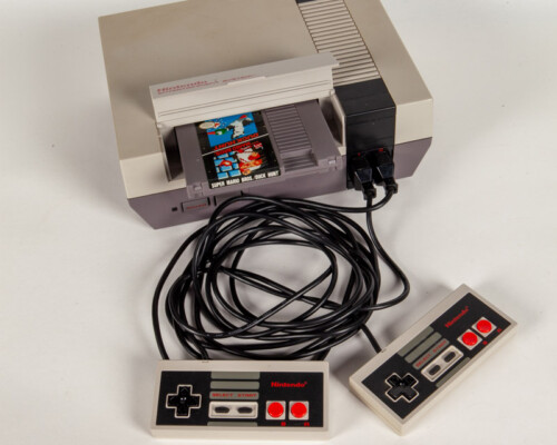 Nintendo Entertainment System with two controllers and a cartridge in the tray.