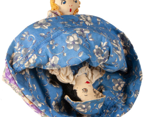 Reversible doll with both faces showing, blue and pink floral dress pattern.