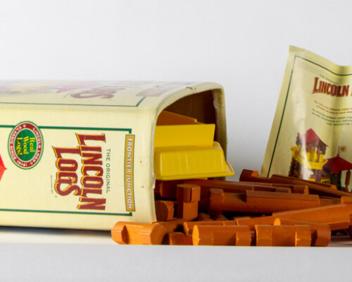Lincoln Logs package opened up showing the brown wooden logs and instructions pack.