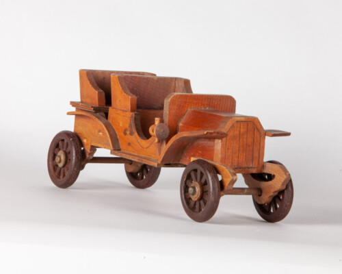 Wooden depiction of early automobile. Multiple colors of wood.