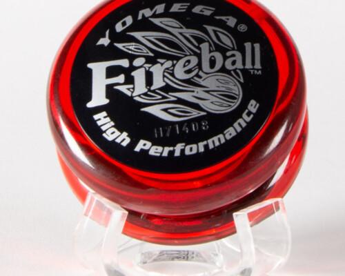 """Red """"Yomega Fireball"""" Yo-yo. Silver text on black sticker attached to clear red plastic Yo-yo."""