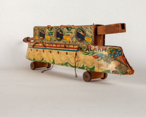 Side of wood and cardboard pull toy shaped like a ship. Painted with naval motifs.