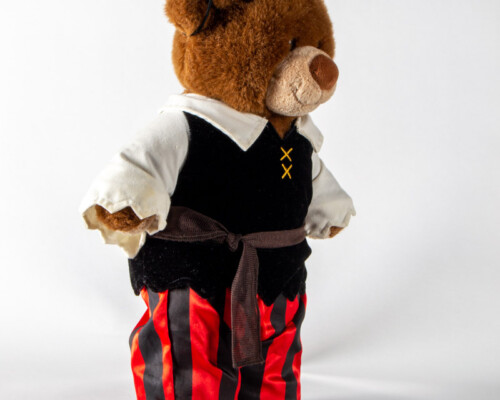 Side view of teddy bear in black, red, and white pirate outfit.