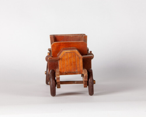 Front of toy car. Wooden depiction of early automobile.