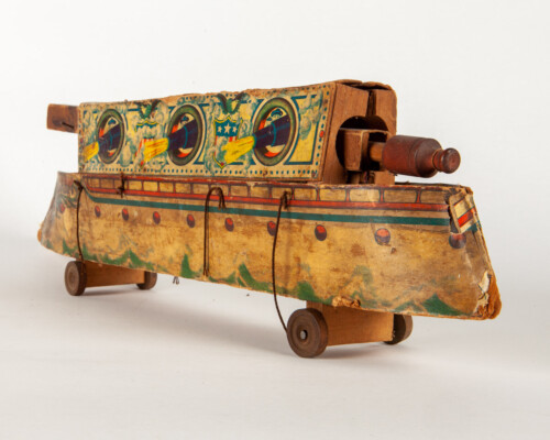 Side view of cardboard and wooden ship pull toy. Painted with US naval motifs.