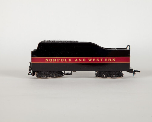 """Side view of red and black coal train car. In gold letters it says """"Norfolk and Western"""""""