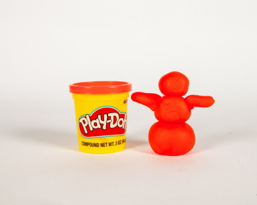 Red Play-Doh snowman next to yellow and red container.