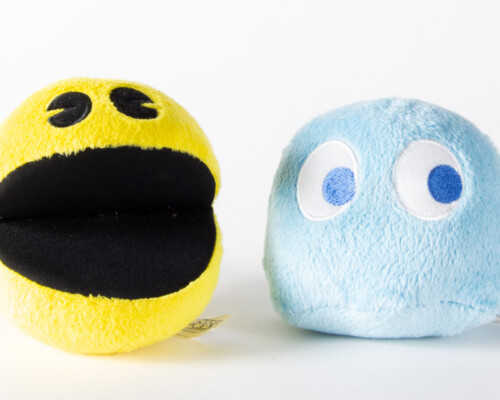 Pacman plush with its mouth open next to a blue ghost plush.